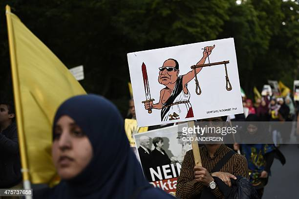 A protester holds up a cartoon depicting Egyptian President Abdel Fattah alSisi as Lady Justice with a bloody sword and balancing gallows scales...