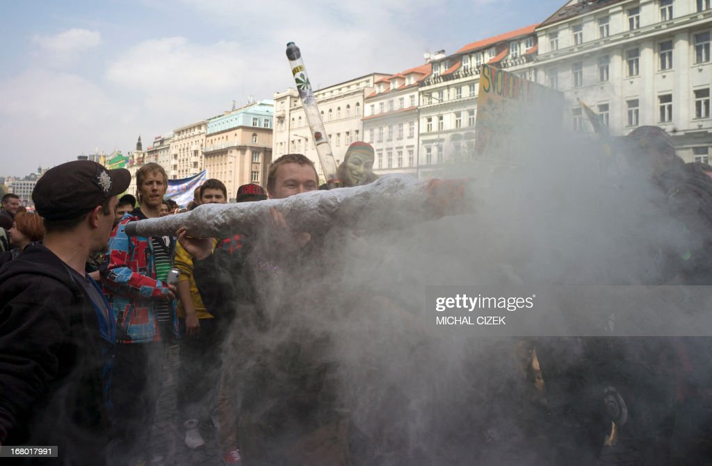 A protester holds up a imitation of a big joint as people take part in a demonstration for the legalization of marijuana in front of the National Museum in Prague on May 4, 2013. AFP PHOTO / MICHAL CIZEK