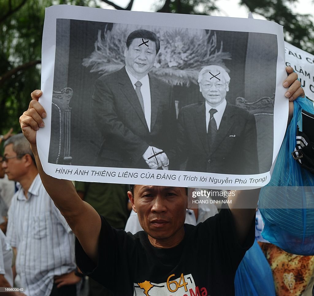 A protester holds up a large photograph showing Vietnamese communist party Secretary General Nguyen Phu Trong (R) shaking hands with his Chinese President Xi Jinping during an anti-China rally in downtown Hanoi on June 2, 2013. Vietnam has detained some 30 anti-China protesters in Hanoi on June 2, amid growing tensions between the communist neighours over rival territorial claims. AFP PHOTO/HOANG DINH Nam