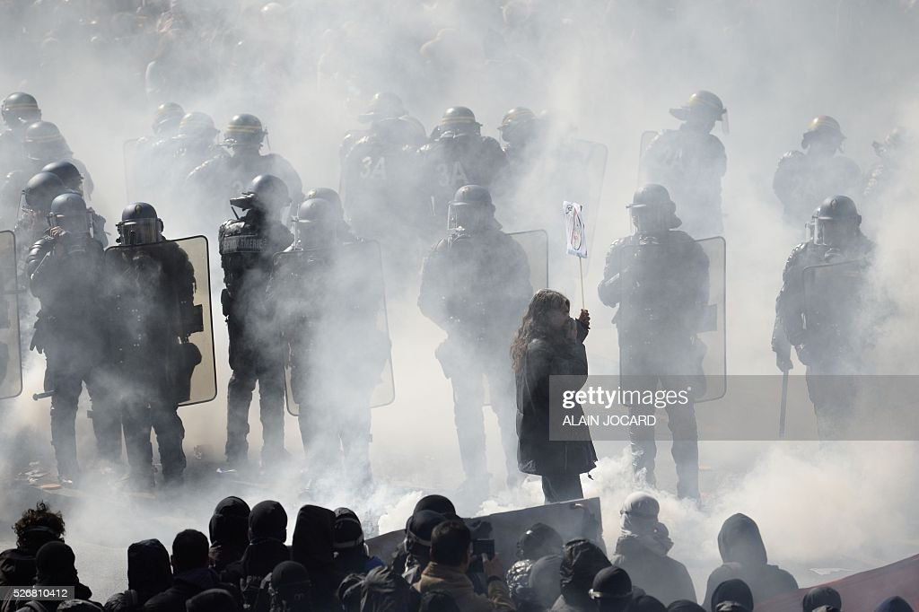 A protester holds up a placard as French anti riot police are surrounded by smoke during a clash during the traditional May Day demonstration in Paris on May 1, 2016.