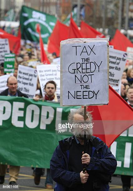 A protester holds up a placard as thousands of people join a mass protest in Dublin Ireland against the government's approach to the economic crisis...