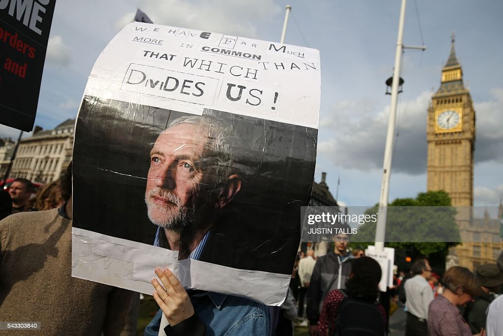 A protester holds up a placard in support of Leader of the opposition Labour Party Jeremy Corbyn outside parliament during a pro-Corbyn demonstration in central London on June 27, 2016. Britain's historic decision to leave the 28-nation bloc has sent shockwaves through the political and economic fabric of the nation. It has also fuelled fears of a break-up of the United Kingdom with Scotland eyeing a new independence poll, and created turmoil in the opposition Labour party where leader Jeremy Corbyn is battling an all-out revolt. TALLIS