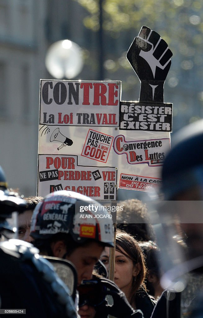 A protester holds up a placard reading 'Against the labour law' during the traditional May Day demonstration in Paris on May 1, 2016.