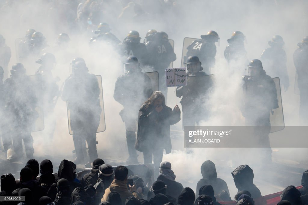 A protester holds up a placard reading 'Labour law equals TAFTA law' as French anti riot police are surrounded by smoke during a clash during the traditional May Day demonstration in Paris on May 1, 2016.