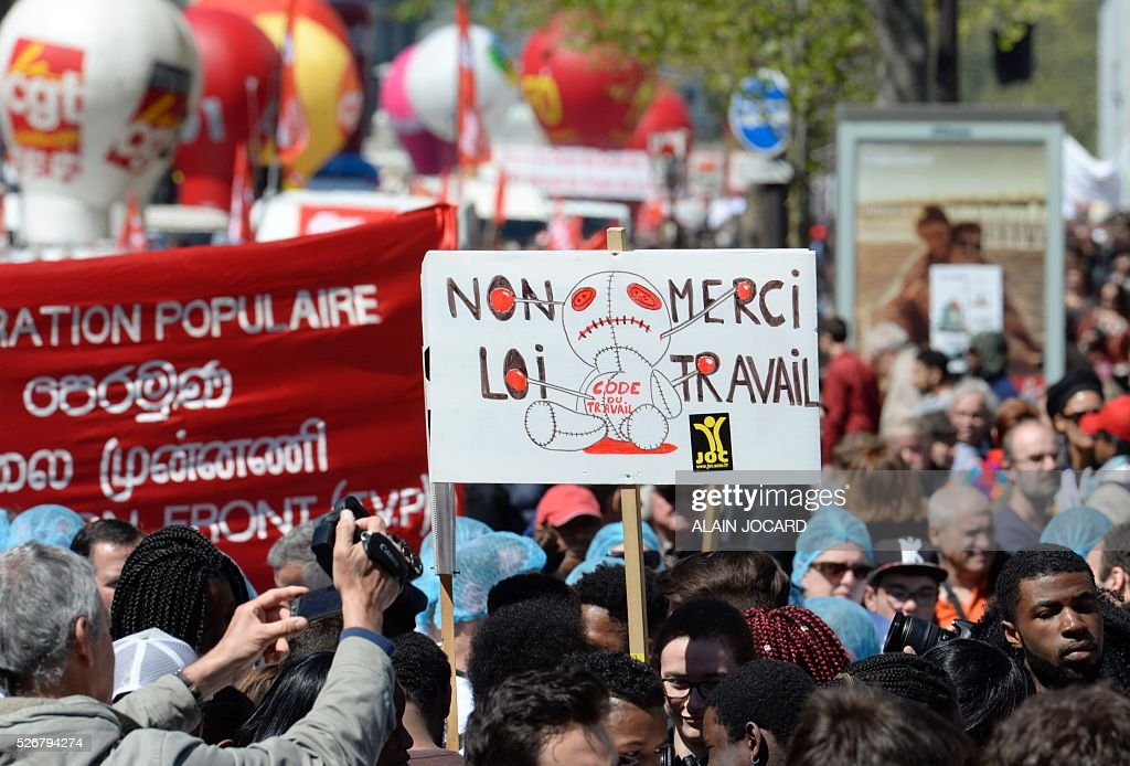 A protester holds up a placard reading 'Labour law - no thank you' as people take part in the traditional May Day demonstration in Paris on May 1, 2016.