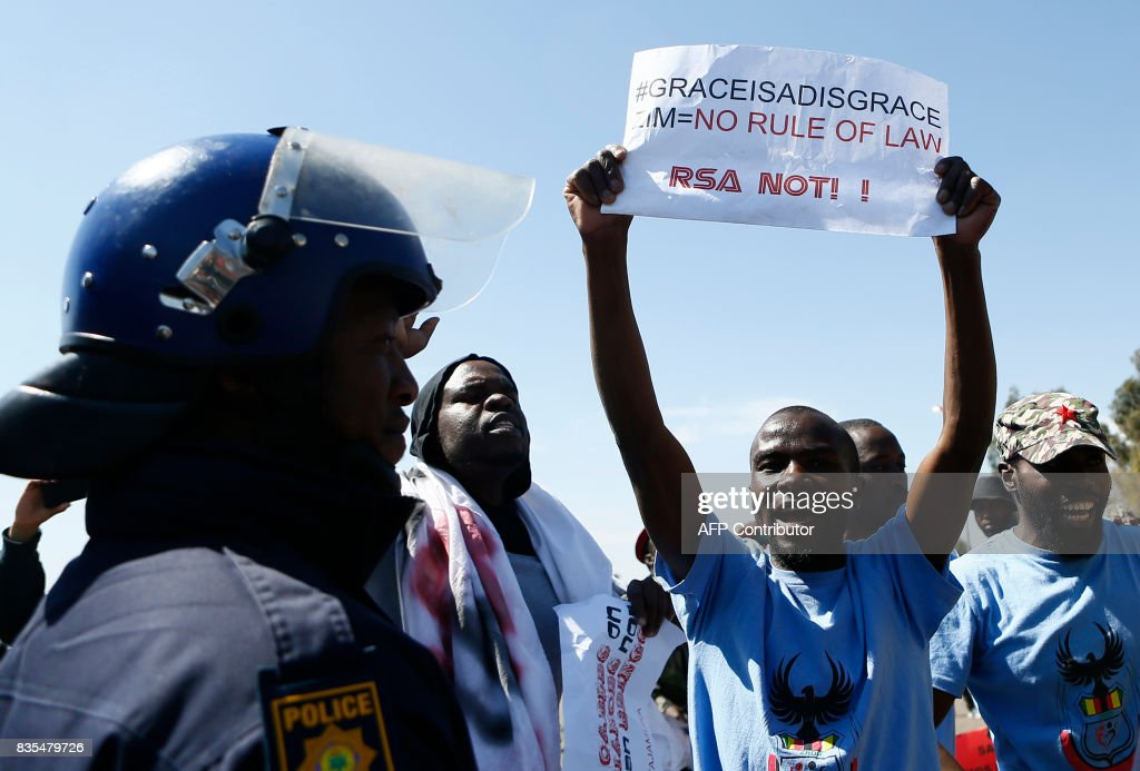 A protester holds up a sign as other from various Southern African Development Community (SADC) countries demonstrate near the entrance to Department of International Relations and Cooperation where the SADC Summit is being held in Pretoria on August 19, 2017. The protesters are demanding for the Democratic Republic of Congo (DRC) President Joseph Kabila to step down, and also calling on South Africa to set an example in the handling of the Zimbabwe's first lady Grace Mugabe who is seeking diplomatic immunity for an alleged assault in South Africa on a a 20-year-old model. / AFP PHOTO / Phill Magakoe