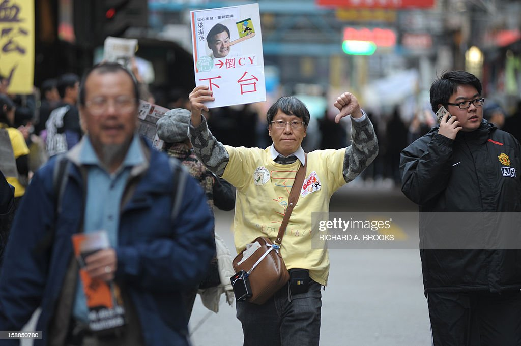 A protester holds up a sign illustrating new Hong Kong Chief Executive Leung Chun-ying as Pinocchio, as thousands take to the streets calling for Leung to step down in Hong Kong on January 1, 2013. Organisers have said they expected 50,000 people to join the New Year's Day march against Leung Chun-ying, while pro-government groups staged separate and smaller rallies in support of the Beijing-backed chief executive.