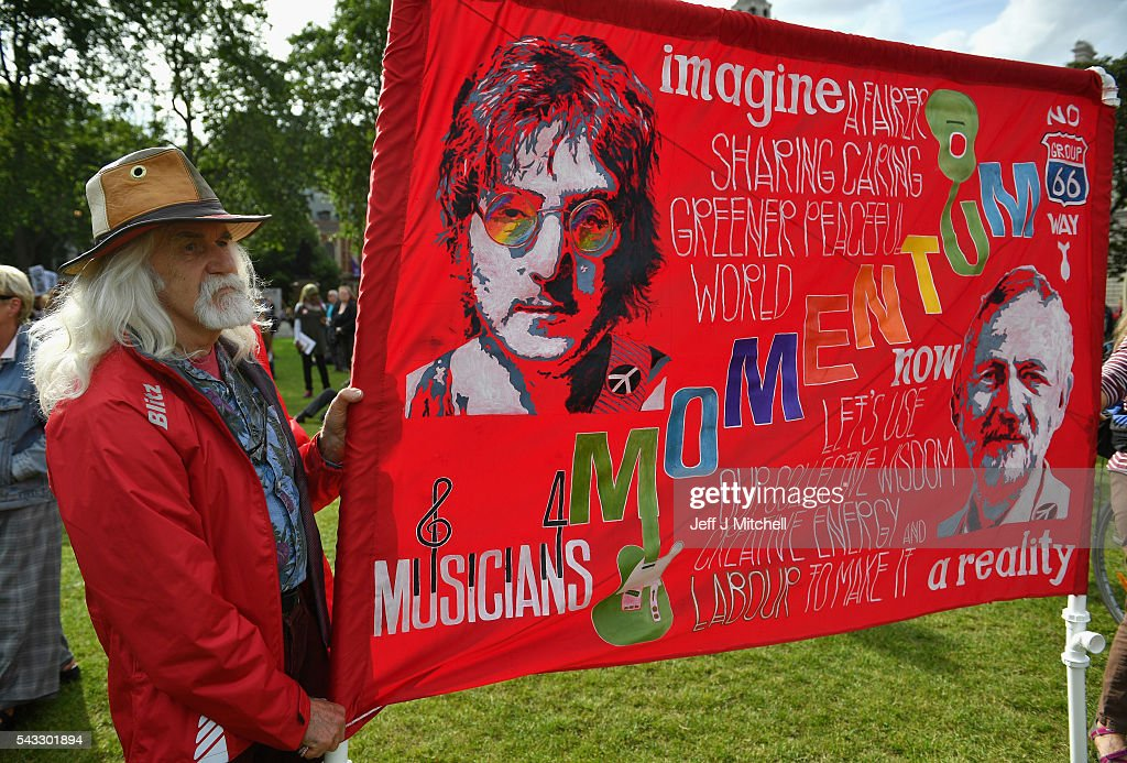 A protester holds up a sign picturing John Lennon and Labour leader Jeremy Corbyn during Momentum's 'Keep Corbyn' rally outside the Houses of Parliament on June 27, 2016 in London, England. The Labour Leader has seen mass resignations from the Shadow Cabinet in the wake of the UK Vote for Brexit. His support group, Momentum, have recorded more than 1000 new members in the same period.