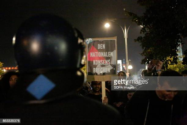 A protester holds up a sign that reads 'Break the National consent' A police officer is watching Hundreds of protesters gathered outside a club near...
