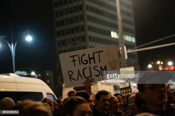 A protester holds up a sign that reads 'Fight racism' Hundreds of protesters gathered outside a club near the central Alexanderplatz in Berlin that...