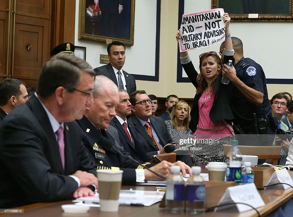 A protester holds up a sign while Defense Secretary <a gi-track='captionPersonalityLinkClicked' href=/galleries/search?phrase=Ashton+Carter&family=editorial&specificpeople=956792 ng-click='$event.stopPropagation()'>Ashton Carter</a> (L) and Chairman of the Joint Chiefs of Staff Gen. <a gi-track='captionPersonalityLinkClicked' href=/galleries/search?phrase=Martin+Dempsey&family=editorial&specificpeople=2116621 ng-click='$event.stopPropagation()'>Martin Dempsey</a> (2ndL) testify before the House Armed Services Committee on Capitol Hill June 17, 2015 in Washington, DC. The committee is hearing testimony on U.S. policy and strategy in the Middle East.