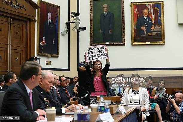 A protester holds up a sign while Defense Secretary Ashton Carter and Chairman of the Joint Chiefs of Staff Gen Martin Dempsey testify before the...