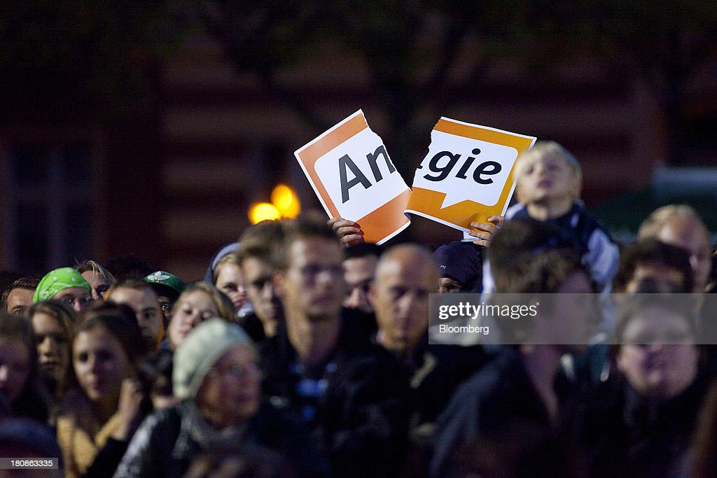 A protester holds up a torn 'Angie' sign, in reference to Angela Merkel, Germany's chancellor and party leader of the Christian Democratic Union (CDU), during an election rally in Potsdam, Germany, on Monday, Sept. 16, 2013. Delayed plans for a financial transaction tax in 11 European states would get a fresh push if Chancellor Angela Merkel enters a coalition with the Social Democrats after Sept. 22 German elections, top SPD members said. Photographer: Krisztian Bocsi/Bloomberg via Getty Images