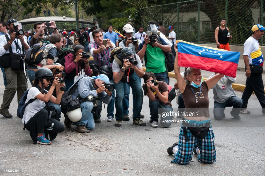 A protester holds up a Venezuelan national flag during the anti-government protests in Caracas, Venezuela on March 12, 2014. Three people including a university student and a National Guard member, were shot death and several others injured on Wednesday during the anti-government protests in Venezuela.