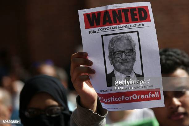 A protester holds up a 'wanted poster' showing a picture of the chief executive of Local authority landlords KCTMO as people call for justice for...
