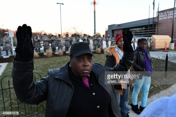 A protester holds up her hands as National Guard troops secure the police station in Ferguson Missouri on November 25 2014 a day after violent...