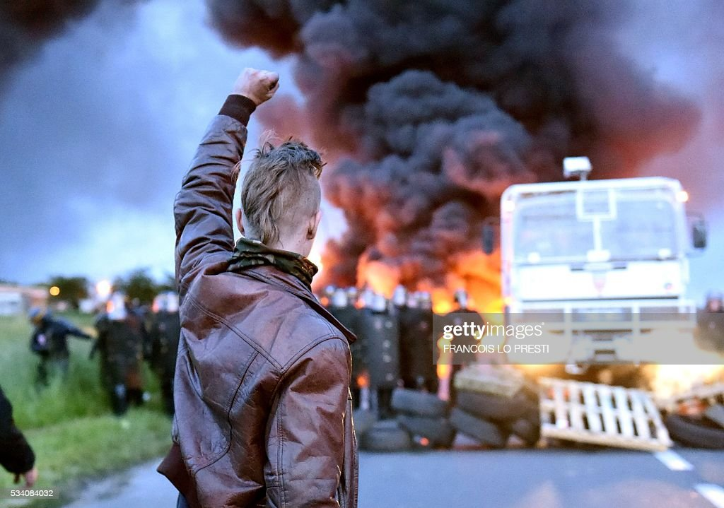A protester holds up his fist as riot police prepare to intervene to disperse refinery worker holding a blockade of the oil depot of Douchy-Les-Mines to protest against the government's proposed labour reforms, on May 25, 2016. Refinery workers stepped up strikes that threaten to paralyse France weeks ahead of the Euro 2016 tournament as the government moved to break their blockades, escalating a three-month tug-of-war over labour reforms. / AFP / FRANCOIS