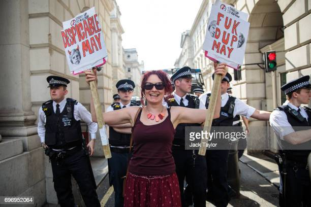 A protester holds up placards in front of a line of police during a demonstration on Whitehall against British Prime Minister Theresa May on June 17...