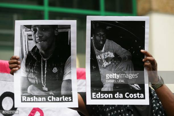 A protester holds up printed photographs of Edir Da Costa a 25yearold man who died in hospital after being detained by police in London and Rashan...