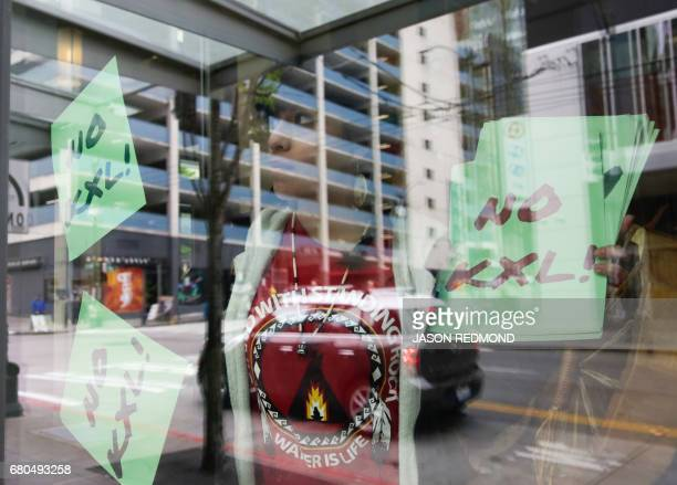 A protester holds up sings in a window as indigenous leaders and climate activists disrupt business at a Chase Bank branch to protest funding tar...
