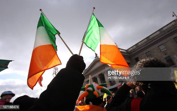 A protester holds up two Irish flags in front of the General Post Office in Dublin on November 27 2010 against savage cutbacks About 50000 Irish...