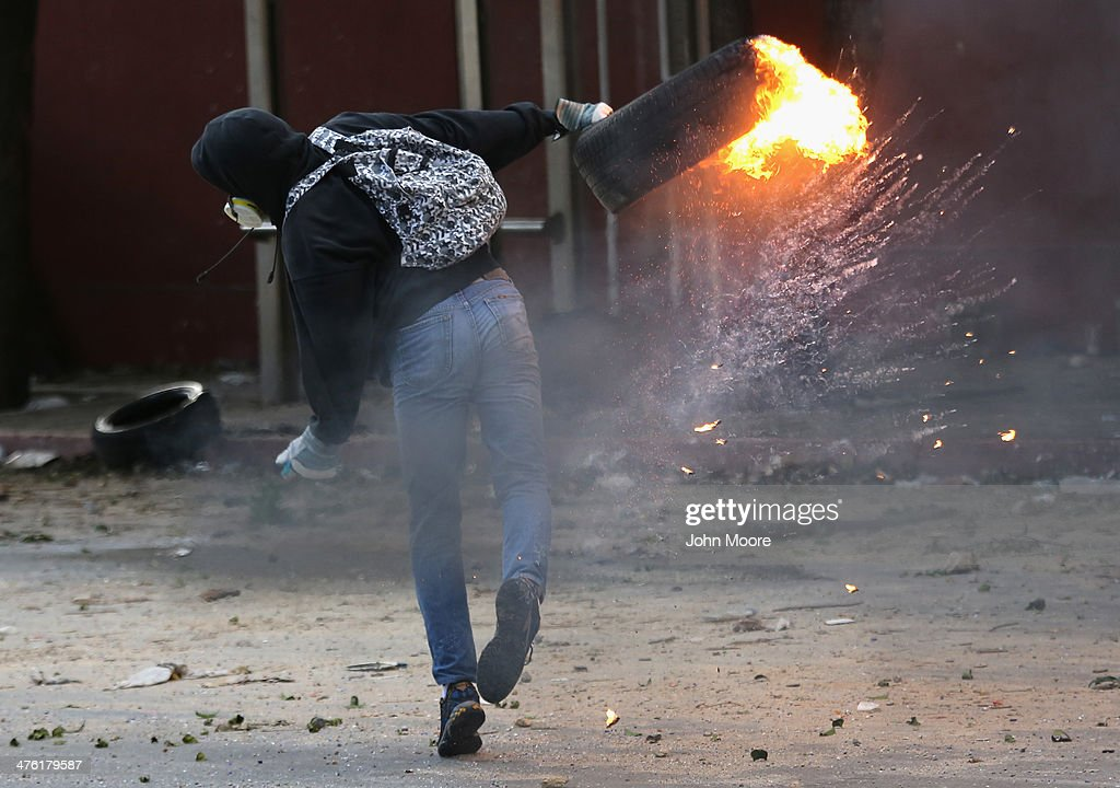 A protester hurls a burning tire at national guard troops during an anti-government demonstration on March 2, 2014 in Caracas, Venezuela. Venezuela has one of the highest inflation rates in the world, and opposition supporters have protested for almost three weeks, virtually paralyzing business in much of the country.