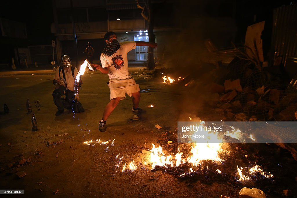 A protester hurls a molotov cocktail at national guard troops during an anti-government demonstration on March 2, 2014 in Caracas, Venezuela. Venezuela has one of the highest inflation rates in the world, and opposition supporters have protested for almost three weeks, virtually paralyzing business in much of the country.