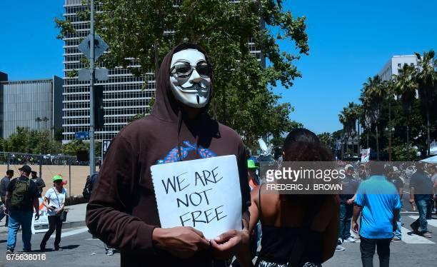 A protester in a Guy Fawkes mask carries a sign that reads 'We Are Not Free' as May Day protesters converge on downtown Los Angeles California May 1...