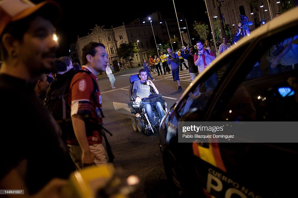 A protester in a wheelchair demonstrates in front of a police car near Cibeles Square on May 15, 2012 in Madrid, Spain. Spain's Indignant movement has prepared events across Spain to mark the first anniversary of their movement, formed to protests against corruption in politics, the economic crisis and the high unemployment rate. In the last 4 days police has arrested 18 demonstrator and has been accused of using violence in some occasions. The movement anniversary coincides with Madrid's regional festivities.