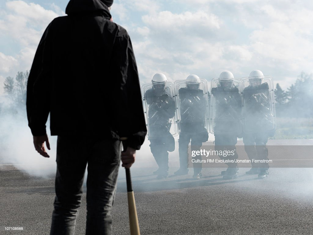 Protester in front of policemen : Stock Photo