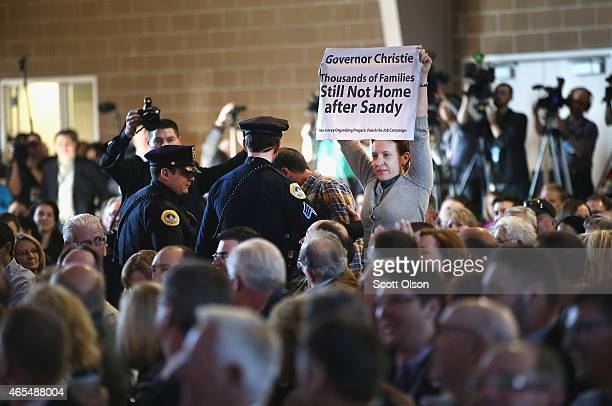 A protester interupts New Jersey Governor Chris Christie as he fields questions from Bruce Rastetter at the Iowa Ag Summit on March 7 2015 in Des...