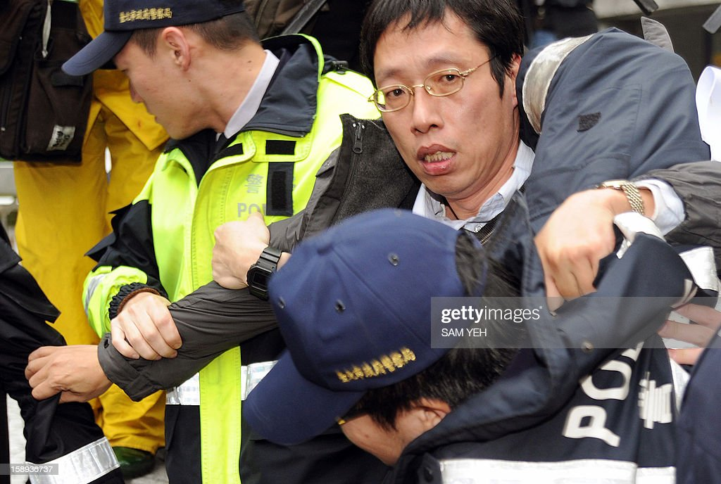 A protester (top R) is arrested by police during an animal rights demonstration in front of the Taiwan government's agriculture council in Taipei on January 4, 2013. The Taiwan Society for the Prevention of Cruelty to Animals demanded the agriculture ministry stop boycotting an animal protection law that the parliament is scheduled to review later this month and demanded the government stop putting down stray animals. AFP PHOTO / Sam Yeh