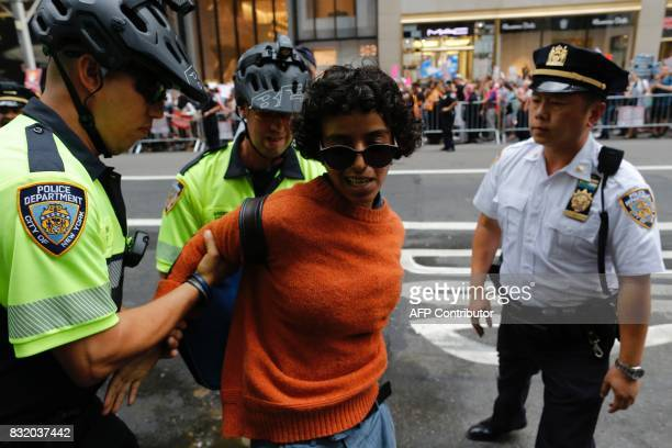 A protester is arrested by police near Trump Tower during a demonstration against attacks on immigrants under the policies of US President Donald...
