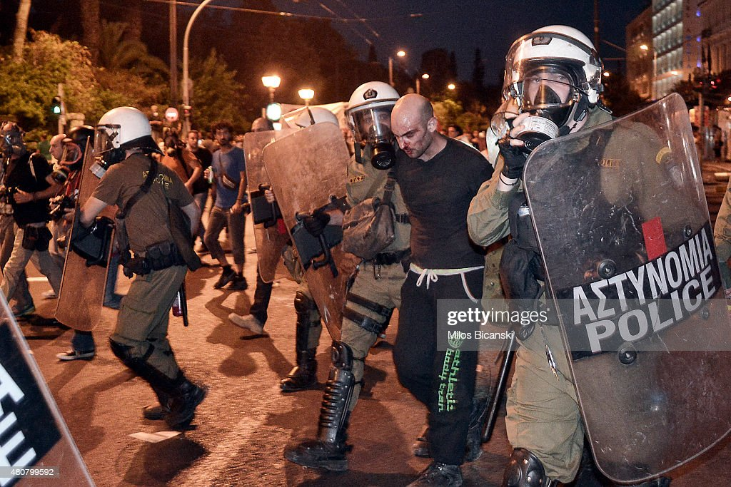 A protester is arrested by riot police following clashes on July 15 2015 in Athens Greece Antiausterity protesters hurled petrol bombs at police in...
