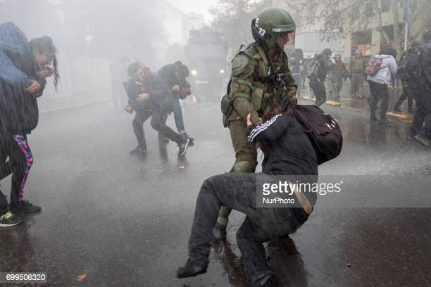 A protester is arrested under water thrown by water cannon cars Led by the Confederation of Chilean Students the march for universal education ends...