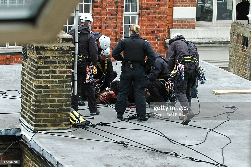 A protester is detained after a precarious rooftop confrontation in Beak Street as arrests are reportedly made as activists occupy a convergence centre of the Stop G8 protest group ahead of next week's G8 summit in Northern Ireland on June 11, 2013 in London, England. Next week will see Enniskillen in Northern Ireland host the two day G8 summit where international leaders including Britain's Prime Minister David Cameron and US President Barack Obama take part in the two day event. The chosen location is only 8 kilometers from the scene of one of Northern Ireland's worst killings back in 1987, however Cameron is confident that it's secluded location will deter any potential trouble.