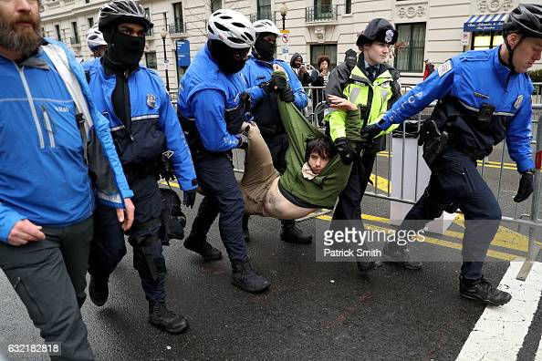 A protester is dragged away from a public access point to the National Mall on 14th Street NW prior to the inauguration on January 20 2017 in...