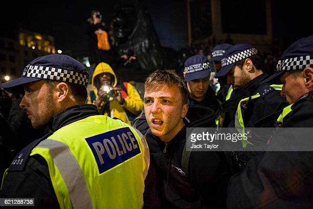 A protester is handcuffed by police in Trafalgar Square during the Million Mask March on November 5 2016 in London England Thousands of demonstrators...