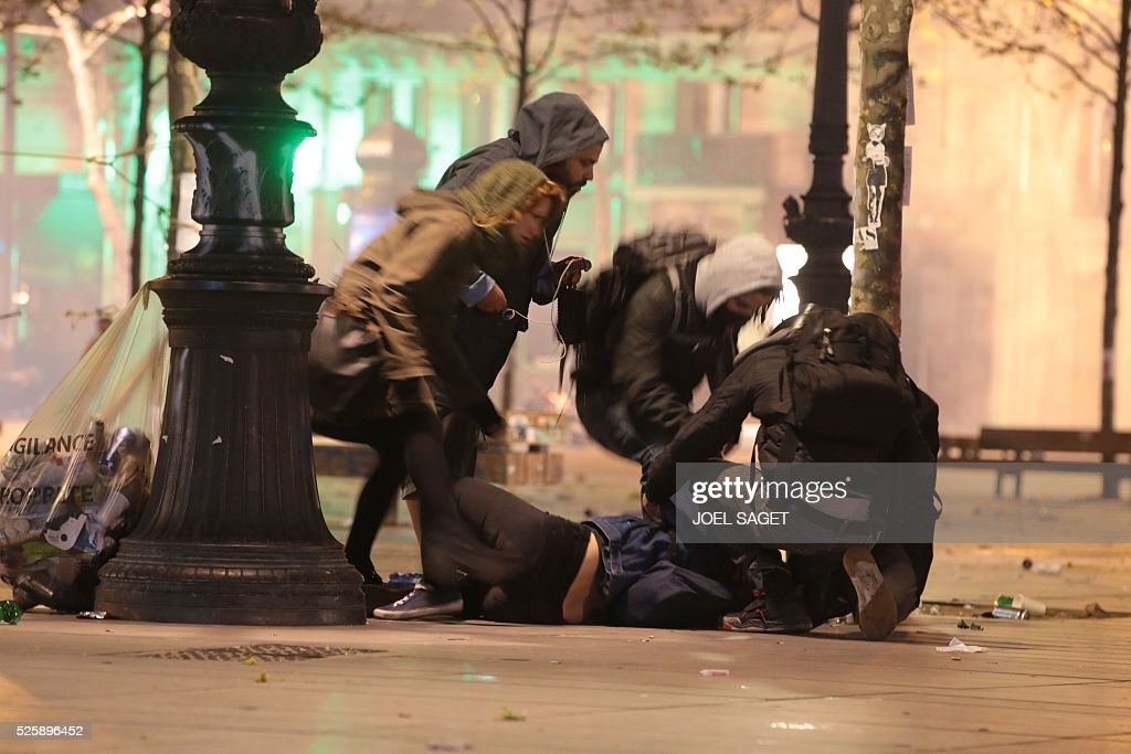A protester is helped at the Place de la Republique in Paris during a protest by the Nuit Debout, or 'Up All Night' movement who have been rallying against the French government's proposed labour reforms on April 29, 2016. Twenty-seven people were arrested and 24 detained during overnight clashes in the French capital as the police dispersed the protesters who began their began movement on March 31 in opposition to the government's proposed labour reforms.
