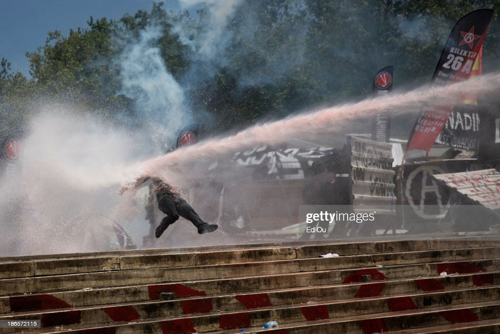 A protester is knocked back by a police water cannon as riot police advance towards Gezi Park from Taksim Square in Istanbul Turkey on June 11 2013 A...