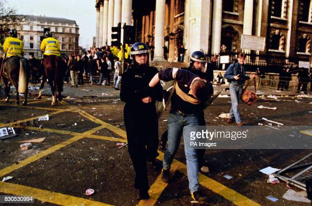 A protester is led away by police officers in riot gear after a protest against the socalled Poll Tax developed into a riot affecting the area around...