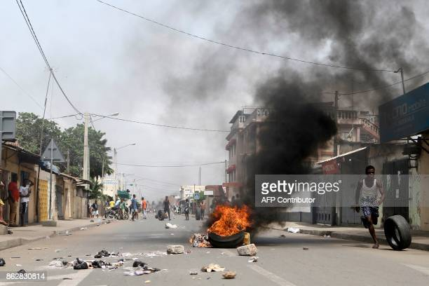 A protester is seen rolling a tire down a street blocked by opposition supporters in Lome on October 18 2017 Protesters erected makeshift barricades...
