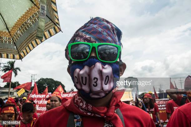 A protester is seen wearing a Duterte mask in an antiDuterte demostration President Duterte delivers his second State of the Nation Address at...