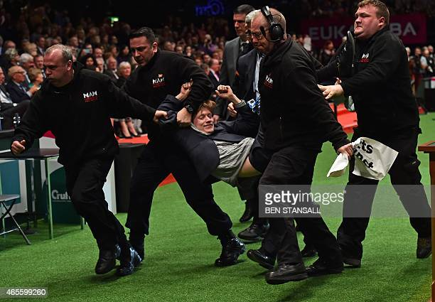 A protester is taken away by security during the trophy presentation at the Crufts Dog Show in Birmingham in central England on March 8 2015 Crufts...