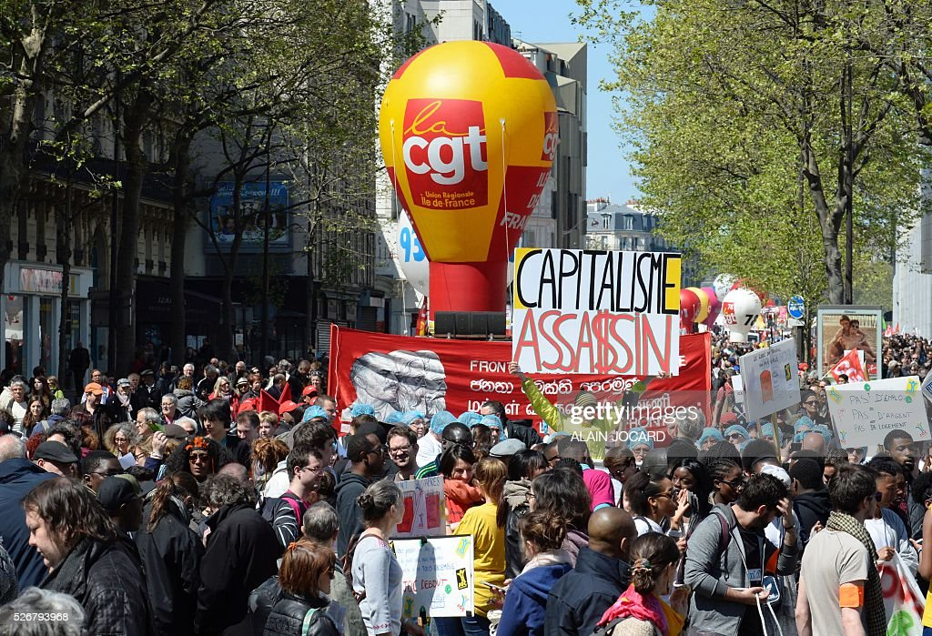 Protester Jean-Baptiste Redde aka Voltuan holds up a placard reading 'Capitalism - assassin' as people take part in the traditional May Day demonstration in Paris on May 1, 2016.