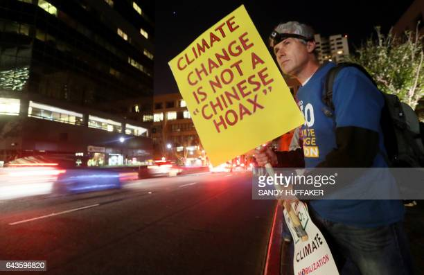 Protester Karl Aldinger displays a sign during a rally against climate change in San Diego California on February 21 2017 The US Senate confirmed...