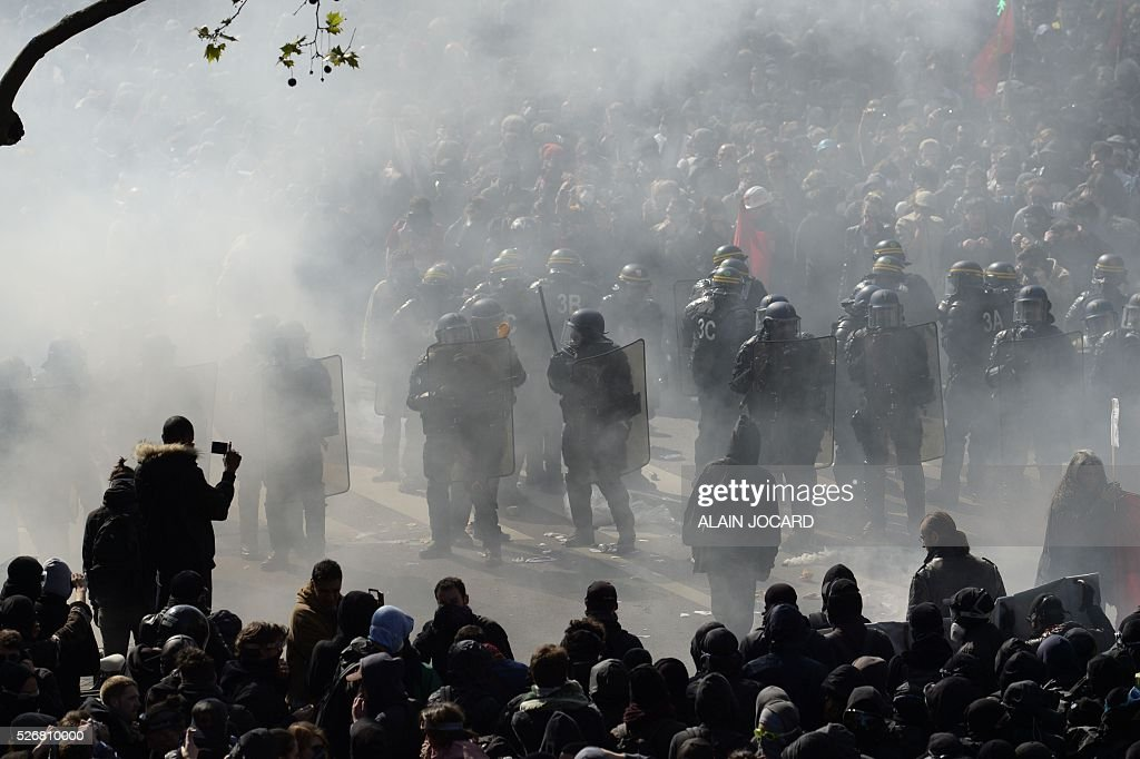A protester kicks a smoke grenade towards French anti riot police during a clash during the traditional May Day demonstration in Paris on May 1, 2016.