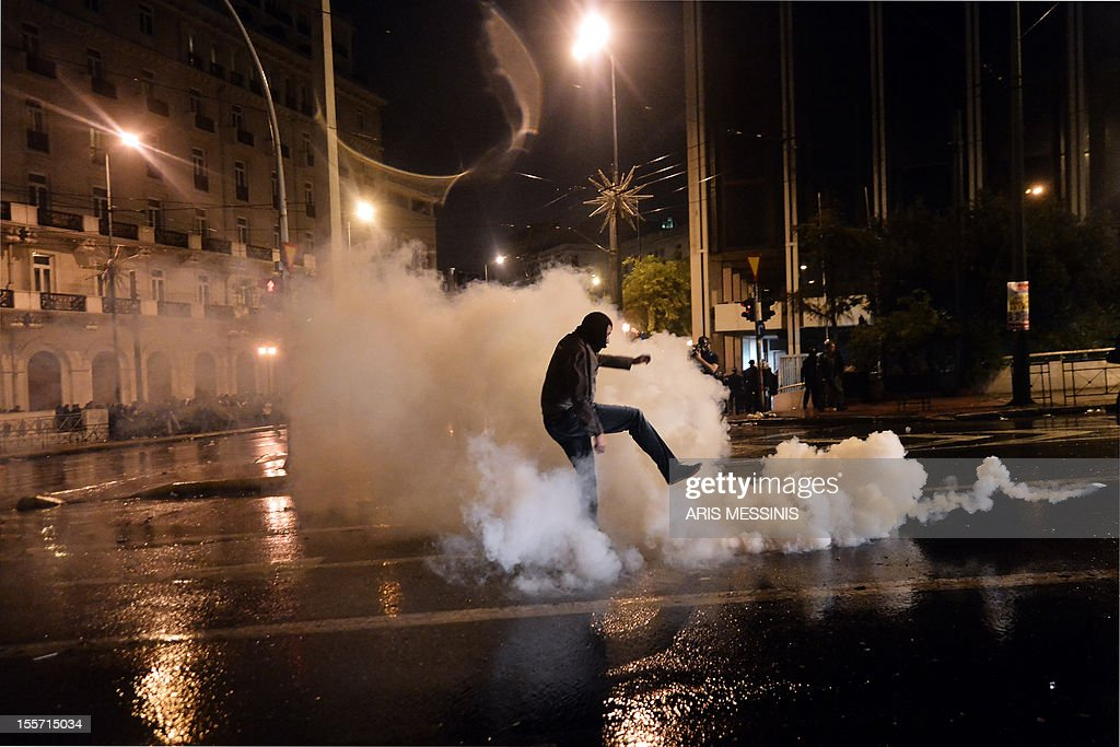 A protester kicks a tear gas canister during a demonstration marking the second day of the 48-hours strike against new austerity measures, in Athens on November 7, 2012. Greek police today used tear gas to disperse demonstrators protesting outside parliament ahead of a key vote on a new round of austerity measures. Some protestors responded by hurling petrol bombs at police forces as the demonstration by some 70,000 people in Athens briefly flared up, an AFP correspondent reported.