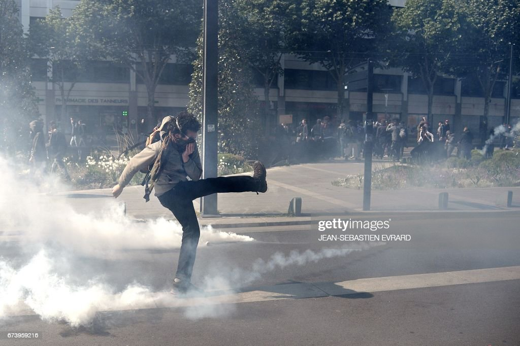 A protester kicks a tear gas round during a demonstration against the results of the first round of the French presidential election in Nantes, western France, on April 27, 2017. Youths gathered to protest against far-right leader Marine Le Pen and former banker Emmanuel Macron, who both qualified on April 23 for the May 7 run-off in France's two-stage presidential election.