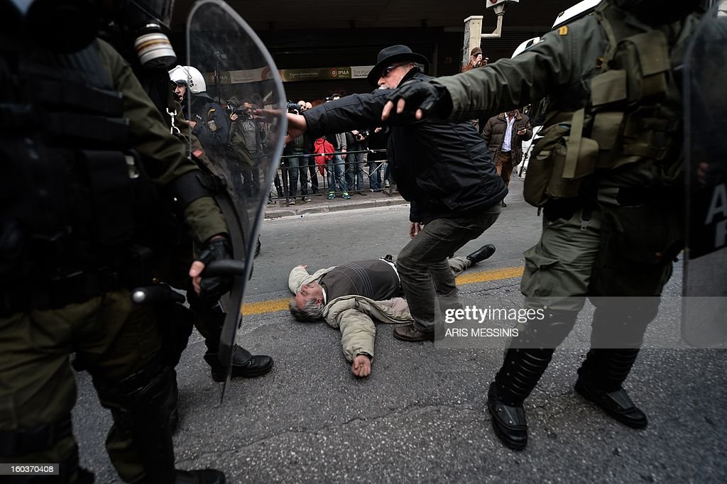 A protester lays on the street outside the Labour Ministry in Athens on January 30, 2013. Police were called in on Wednesday to dislodge around 30 Communist unionists from the labour ministry in a protest against new pension cut plans. The unionists were arrested and police used tear gas outside the building to disperse a larger group of protesters demanding their release.